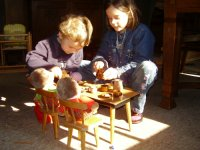 two children at a set table with dolls